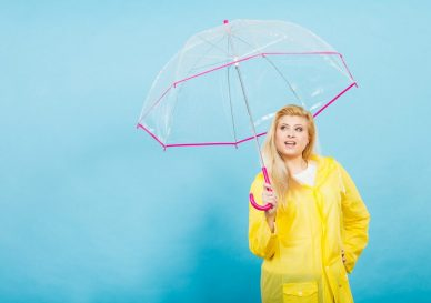 Good mood during rainy day. Happy blonde woman wearing yellow raincoat holding transparent umbrella looking at weather.
