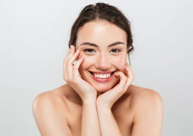 Beauty portrait of a smiling young topless woman with make-up looking at camera isolated over gray background